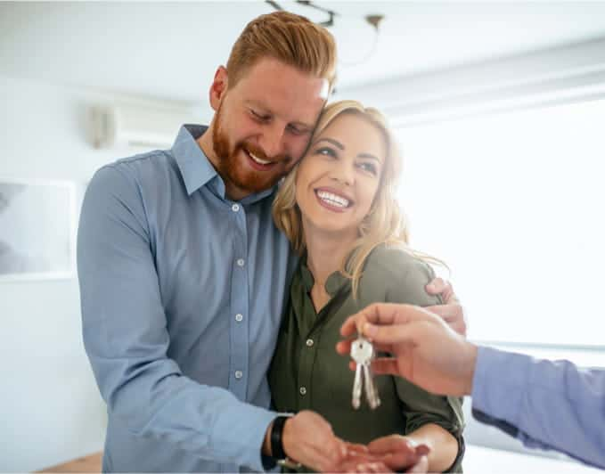 couple receiving keys for house