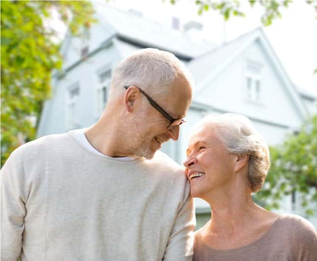 elderly couple standing outside of home