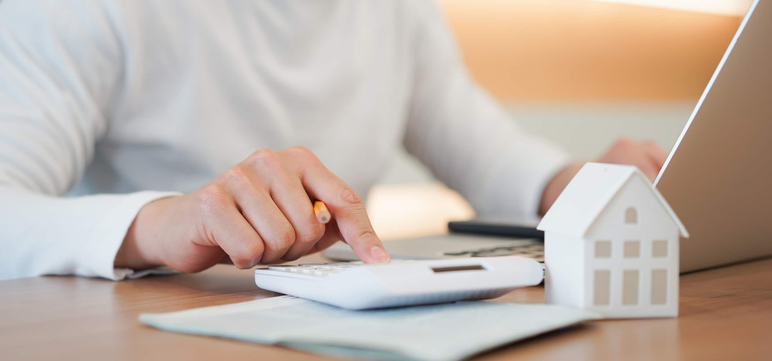 Close up young man hand press on calculator to check and summary expense of home loan mortgage
