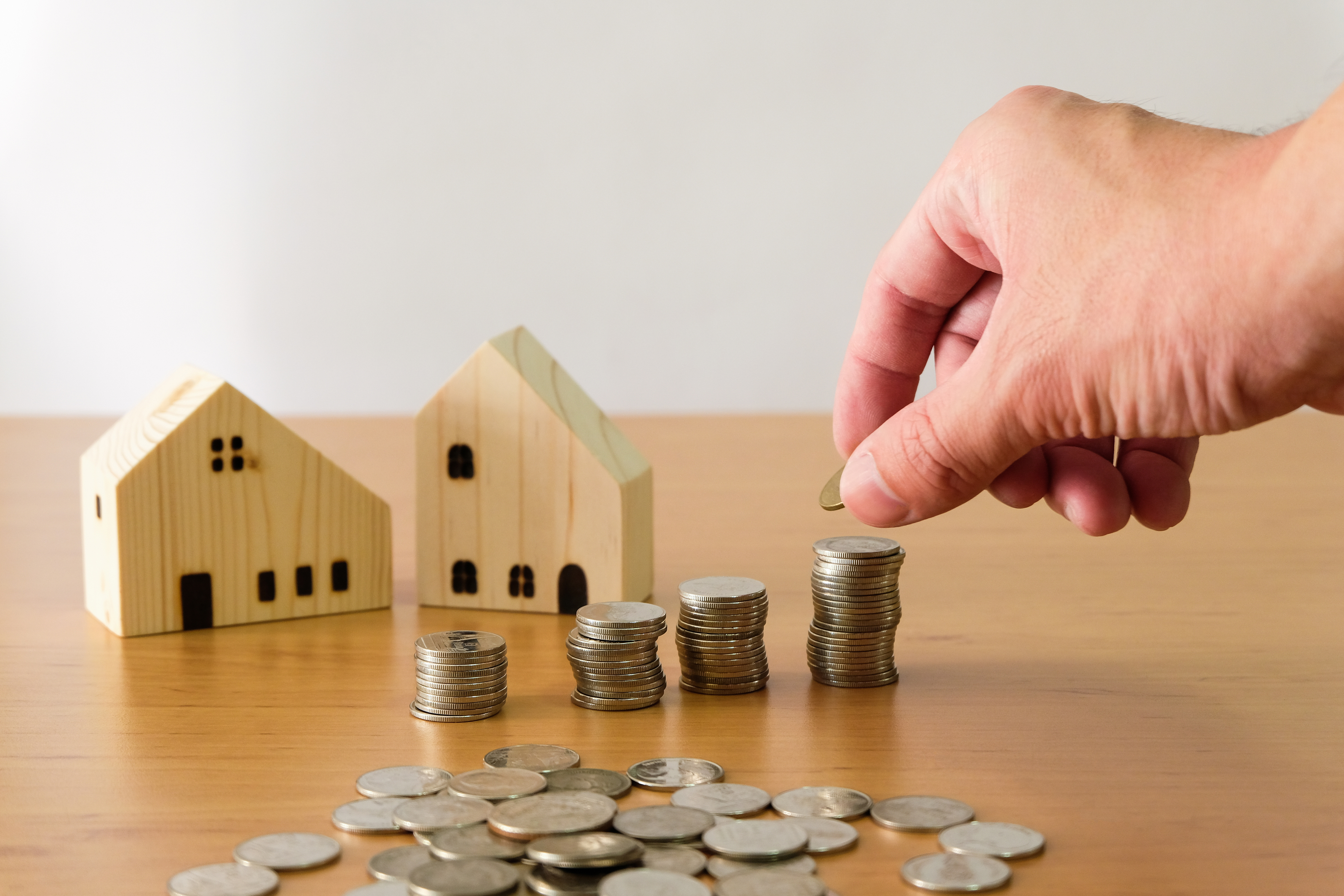 Selective focus Men hand puting coin on stack of money coin for saving for home, property with small wood house on the background. Wealth and saving plan for house mortgage Personal investment concept